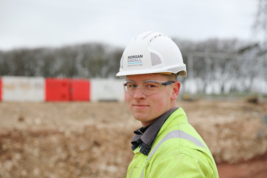 A colleague wearing Personal Protective Equipment, standing in a site environment, looks at the camera