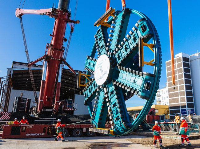 A cutting head from a Tunnel Boring Machine is held by a crane, as it dwarves a team of project colleagues stood alongside it