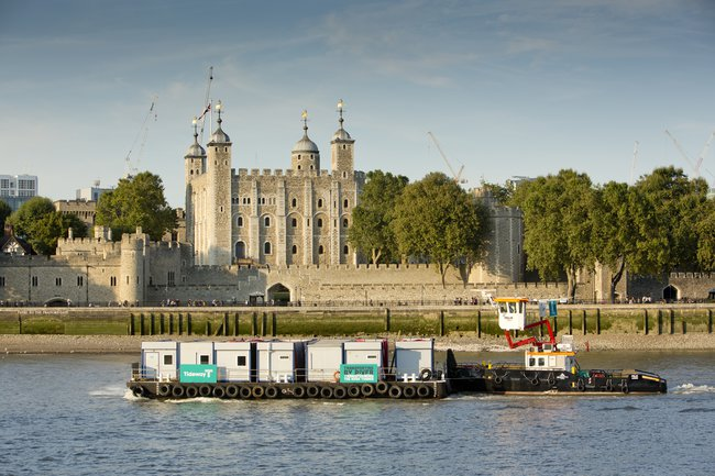 A photograph of one of the barges used to carry materials on the Thames Tideway Tunnel West Section project, passing the Tower of London