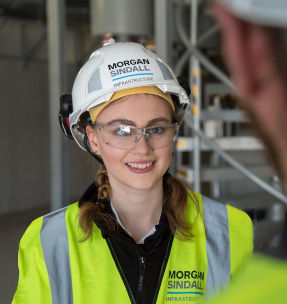 A female colleague wearing PPE and smiling
