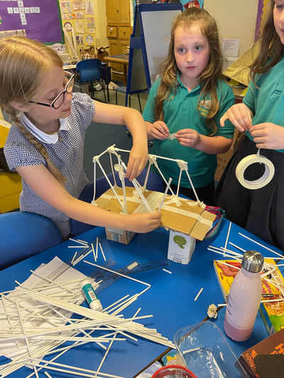 Three pupils from Cummersdale Primary School are stood next to a small paper model of a bridge. One of the pupils is fastening one of the connections on the bridge, made from a paper straw.