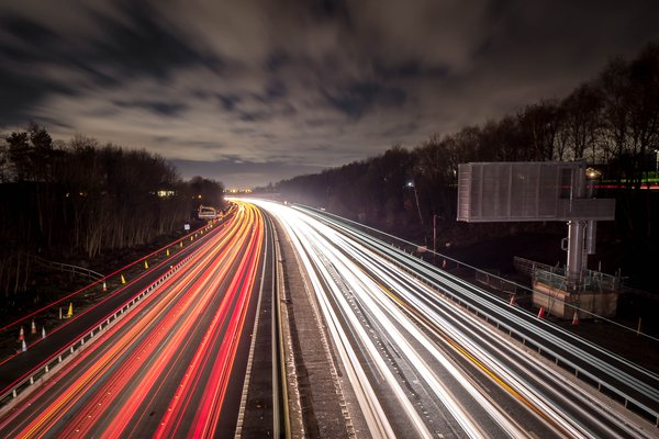 a road at night, lights of cars blurred into long streams