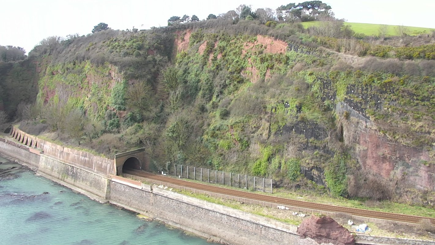 A tunnel is shown emerging from within a hill overlooking the sea