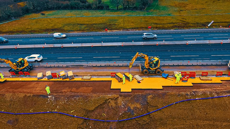 A project team installs specialist rubber material at the side of a road