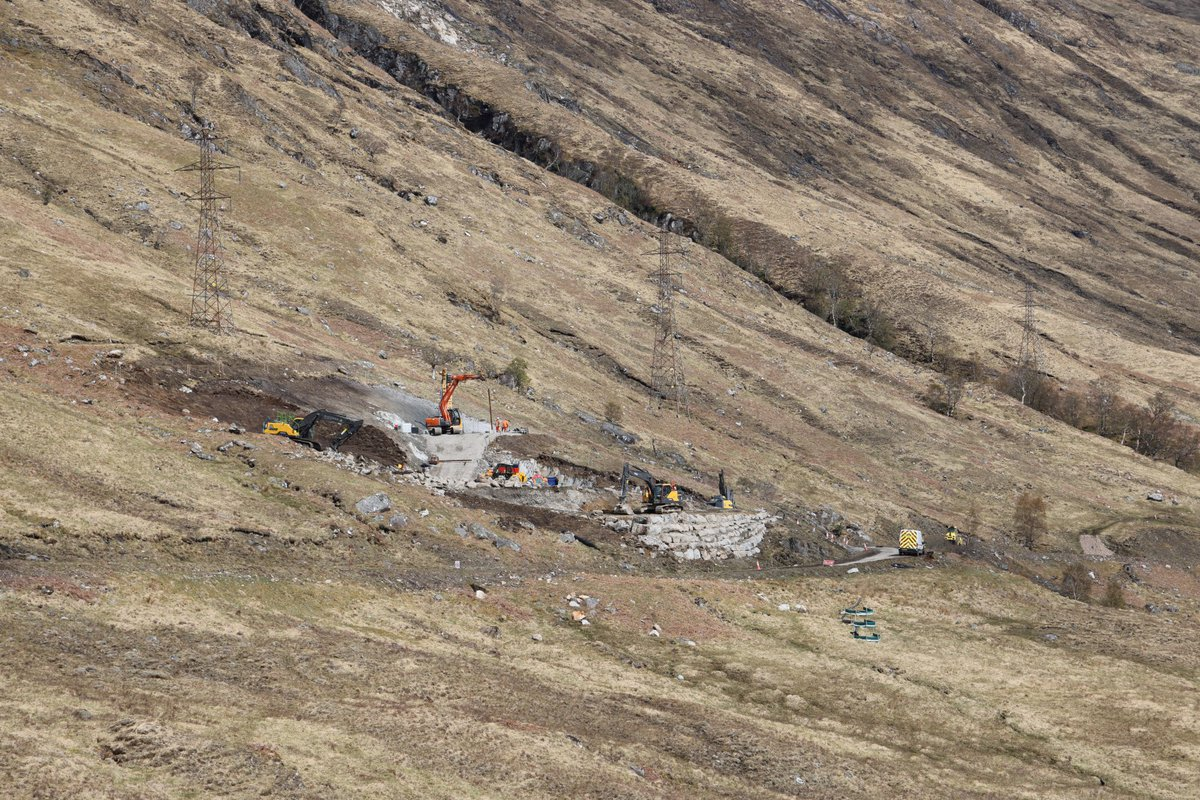 Two diggers are sited on a hillside landscape, with electricity towers visible alongside them