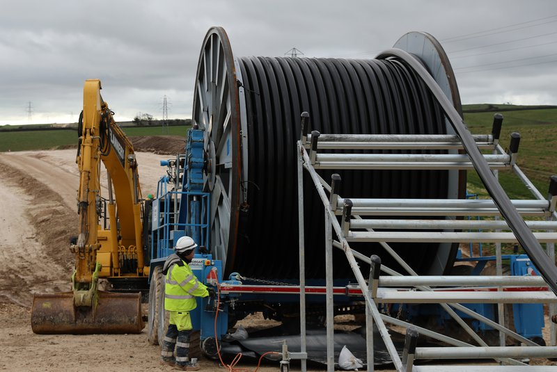 A colleague wearing Personal Protective Equipment stands next to a large reel of industrial cable, and a digger, in an outdoor environment