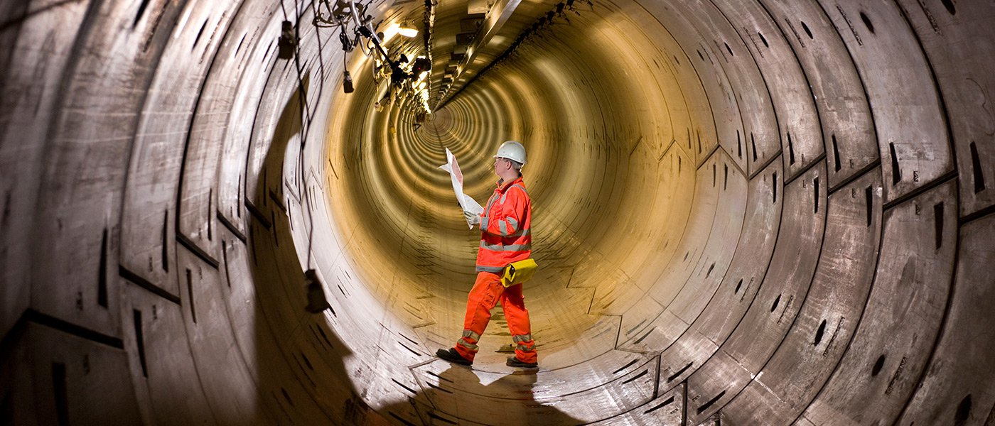 A colleague standing inside a tunnel, wearing PPE, checking a plan