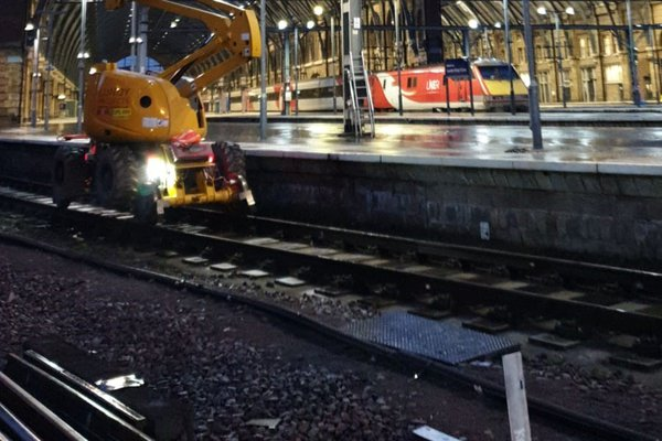 Operatives working on overhead cables at King's Cross, at night.