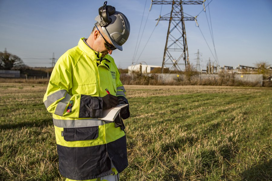 A colleague wearing Personal Protective Equipment stands in a field, writing in a small notebook. Behind him, an electricity tower and cables are visible.