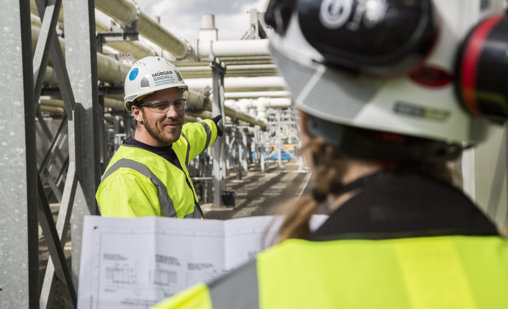 Two colleagues wearing are PPE having a conversation. One, facing us, is pointing at part of the site, where pipes are visible in the background. The other colleague has their head facing away from the camera. They are holding up a set of plans.