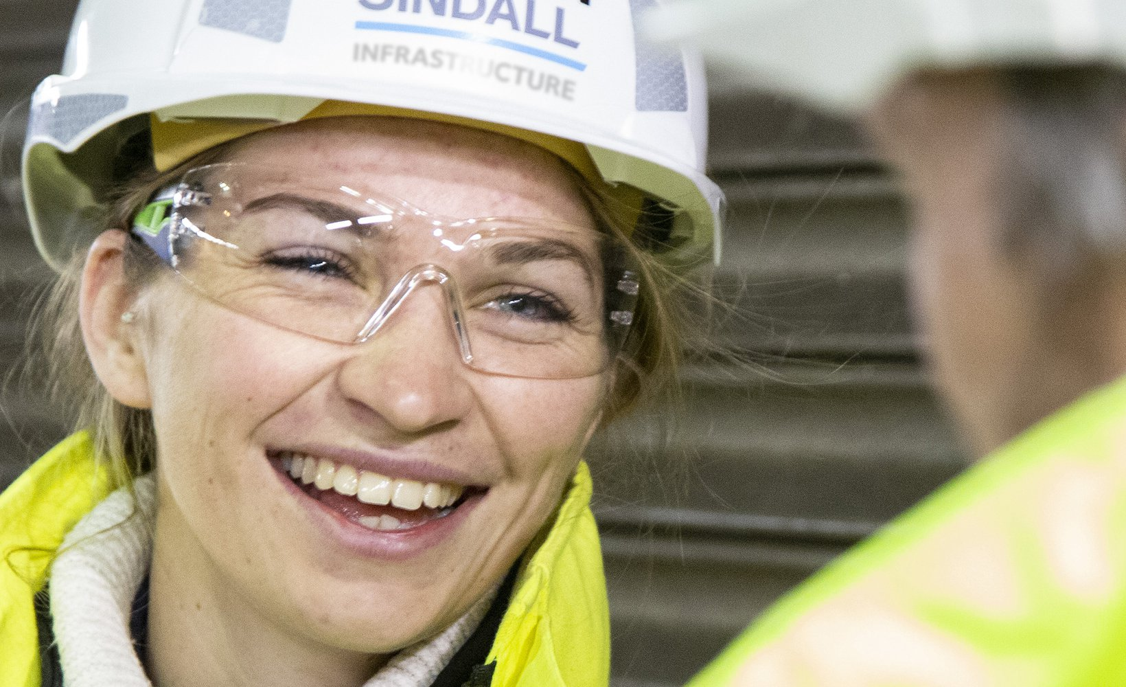 A smiling Morgan Sindall Infrastructure colleague is pictured smiling at a fellow colleague who is facing away from the camera.